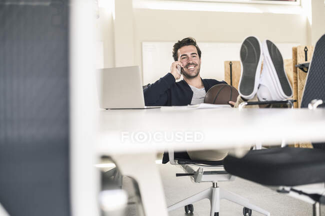 Young businessman sitting in office, with feet on desk, talking on the phone — Stock Photo