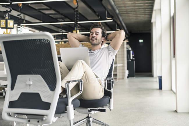 Молодий бізнесмен працює розслабленим у сучасному офісі з ноутбуком на колінах. — стокове фото