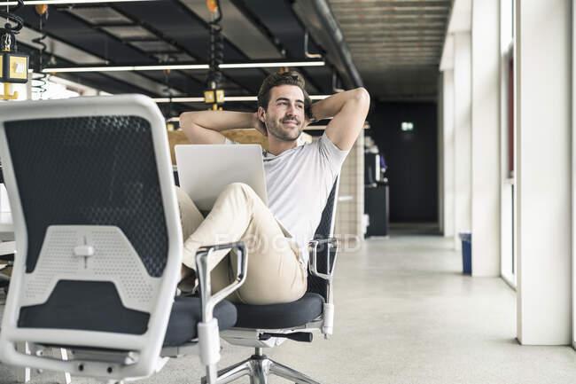 Jovem empresário trabalhando relaxado no escritório moderno, com laptop no colo — Fotografia de Stock