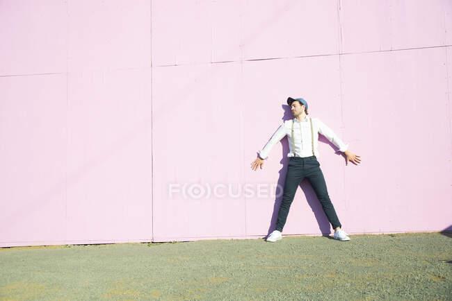 Junger Mann lehnt an pinkfarbener Bauschranke — Stockfoto