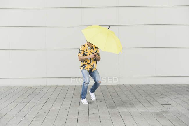 Junger Mann mit Aloha-Hemd und gelbem Regenschirm — Stockfoto