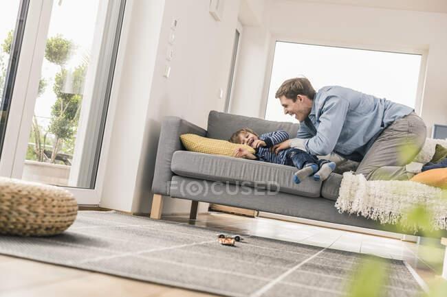 Отец играет со своим сыном, лежит на диване — стоковое фото