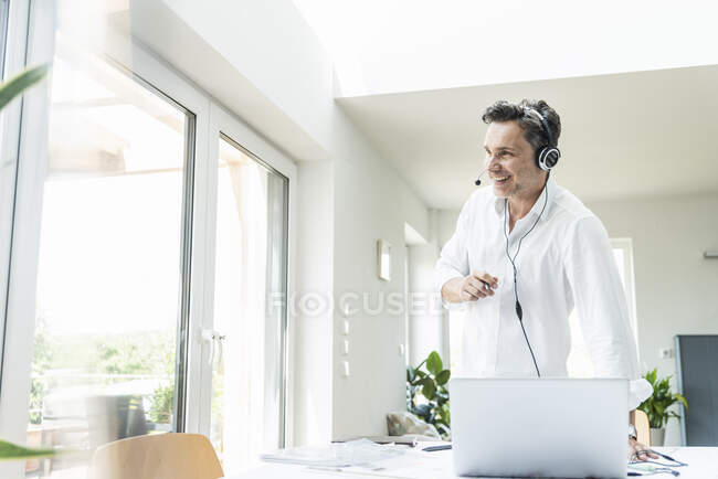 Businessman in bright office having conference call, using headset and laptop — Stock Photo
