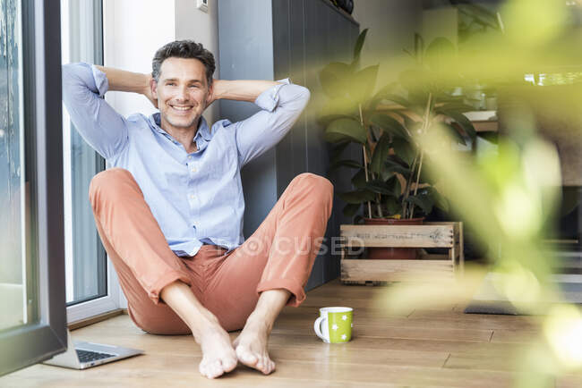 Зрелый мужчина расслабляется дома с чашкой кофе, используя ноутбук — стоковое фото
