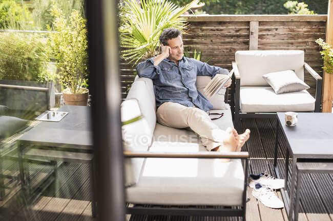 Впевнений чоловік відпочиває на терасі, читаючи книжку — стокове фото