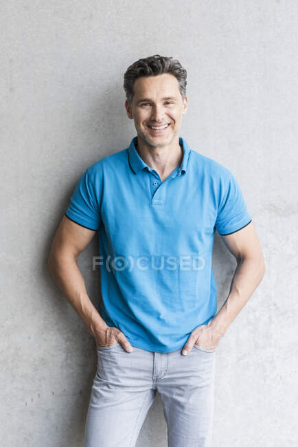 Mature man wearing blue poloshirt, grey wall in the background — Stock Photo