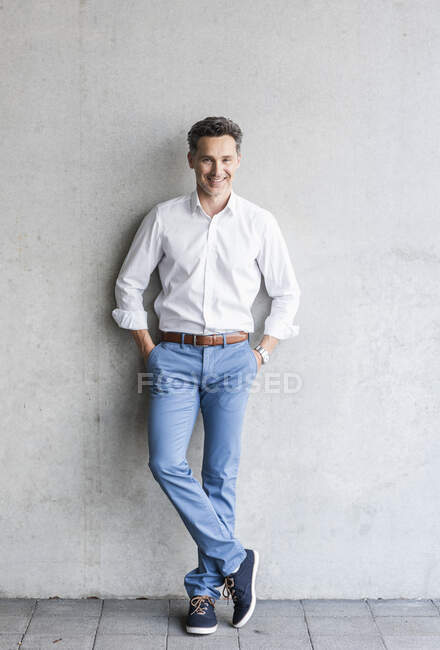 Businessman wearing white shirt, grey wall in the background — Stock Photo