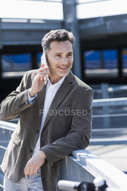 Businessman using smartphone, E-Scooter leaning on railing — Stock Photo
