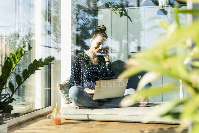 Smiling young woman on cell phone at home — Stock Photo