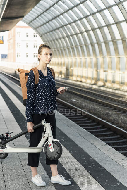 Young woman with electric scooter at the train station — Stock Photo