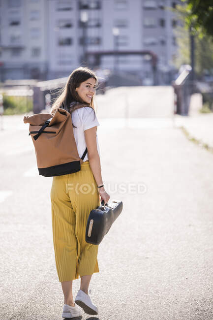 Young woman carrying violin case walking on the street — Stock Photo