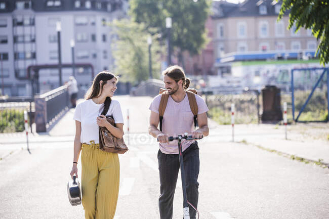 Young couple with electric scooter walking on the street — Stock Photo