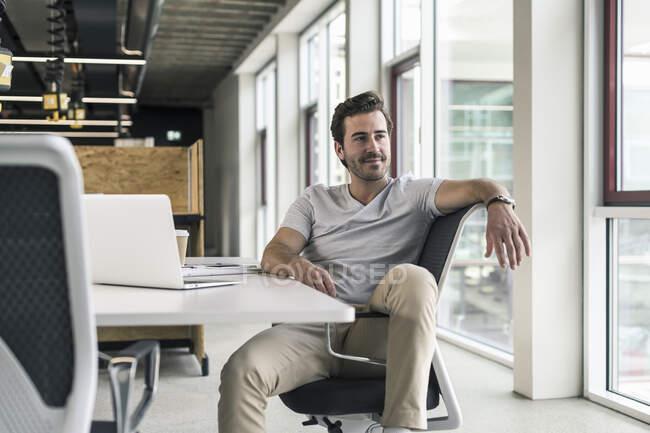 Jovem empresário trabalhando relaxado no escritório moderno, pensando — Fotografia de Stock