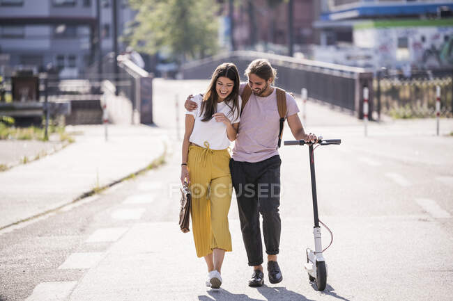 Happy young couple with electric scooter walking on the street — Stock Photo