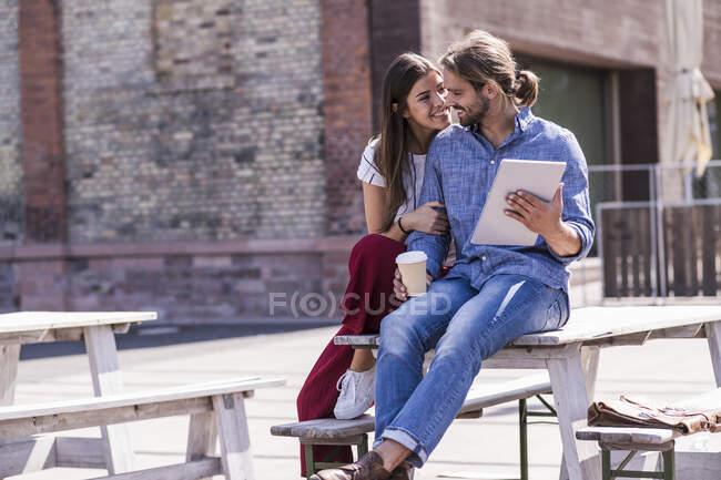 Jovem casal feliz sentado na mesa em um jardim de cerveja com tablet — Fotografia de Stock