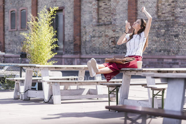 Happy young woman sitting on table in a beer garden using cell phone — Stock Photo