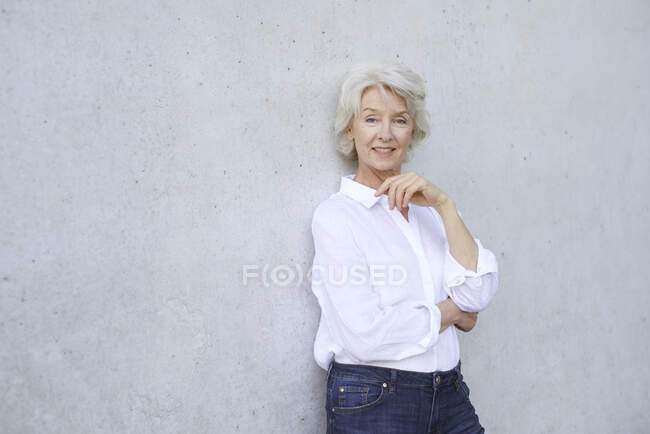 Portrait of smiling mature woman wearing white shirt leaning against concrete wall — Stock Photo