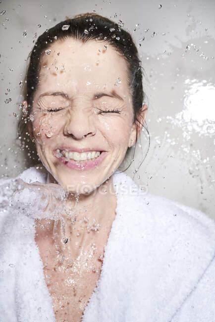 Water splashing into face of happy woman in bathrobe — Stock Photo