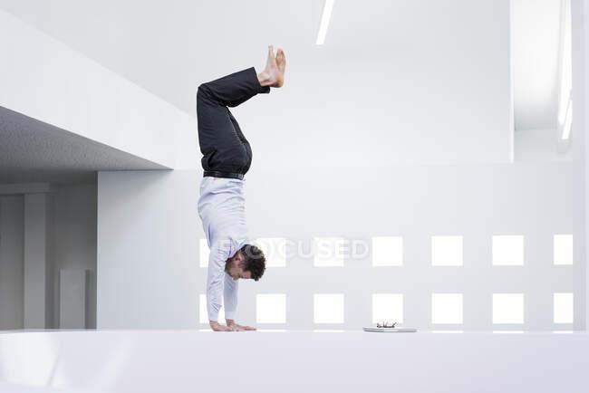 Бизнесмен делает стойку на руках на стойке регистрации в офисе — стоковое фото