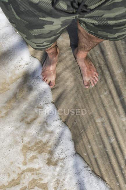 Feet of a man standing on a sandy beach enjoying the waves, Cahuita National Park, Costa Rica — Stock Photo