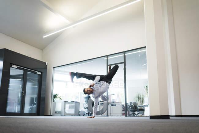 Бизнесмен с сотовым телефоном делает однорукую стойку на руках на полу офиса — стоковое фото