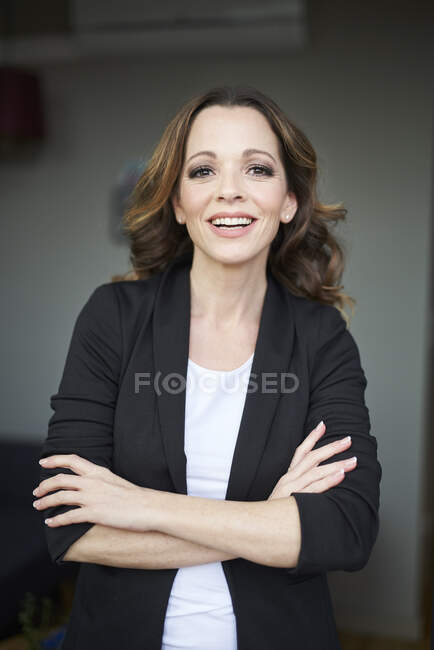 Portrait of happy businesswoman with arms crossed — Stock Photo