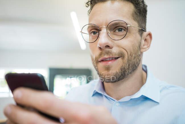 Портрет довірливого бізнесмена, який тримає мобільний телефон. — стокове фото