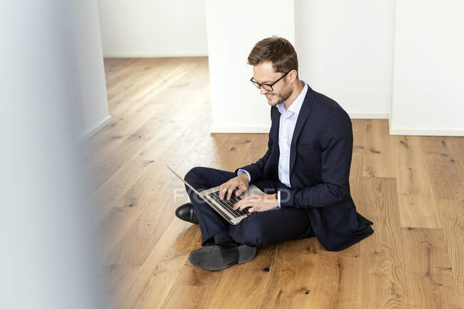 Smiling businessman sitting on the floor using laptop — Stock Photo
