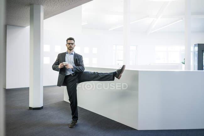 Homme d'affaires avec tasse de café debout sur une jambe dans le bureau — Photo de stock