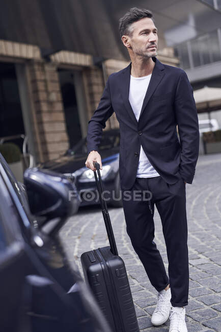 Mature man with trolley in front of a car — Stock Photo