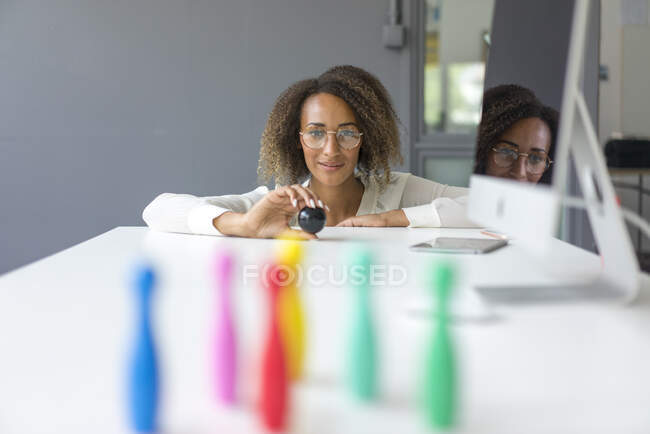 Portrait of smiling young freelancer playing with miniature pins on desk — Stock Photo