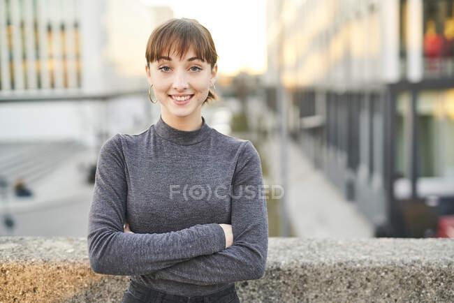 Портрет усміхненої молодої жінки з перехрещеними руками. — стокове фото