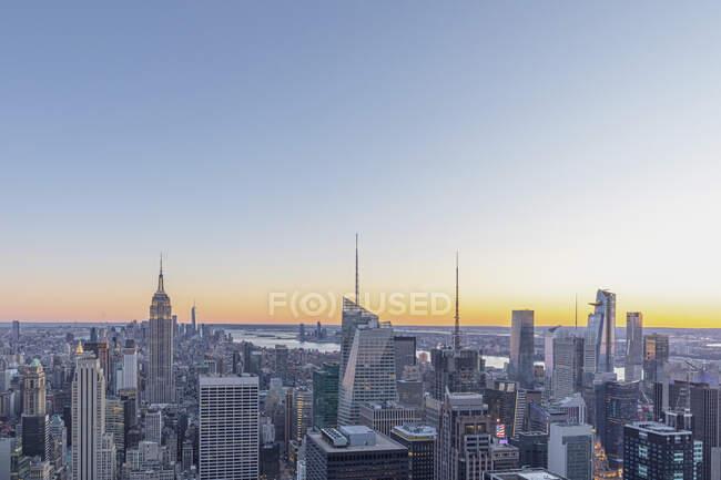 Skyline al atardecer con Empire State Building en primer plano y One World Trade Center en segundo plano, Manhattan, Nueva York, EE.UU. - foto de stock