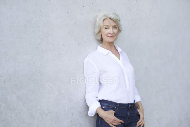 Retrato de mujer madura relajada con camisa blanca apoyada en la pared de hormigón - foto de stock