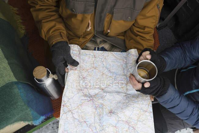 Pareja con bebida caliente y ropa de invierno estudiando hoja de ruta - foto de stock
