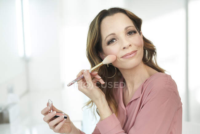 Portrait of smiling woman applying make up at home — Stock Photo