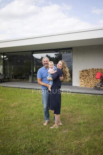 Портрет щасливої родини з трьох осіб, що стоять у своєму домі. — стокове фото