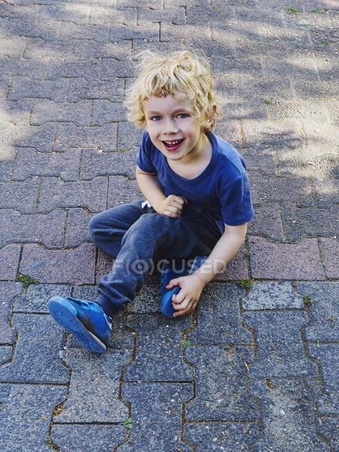 Портрет усміхненого маленького хлопчика, одягненого в синє сидіння на тротуарі. — стокове фото