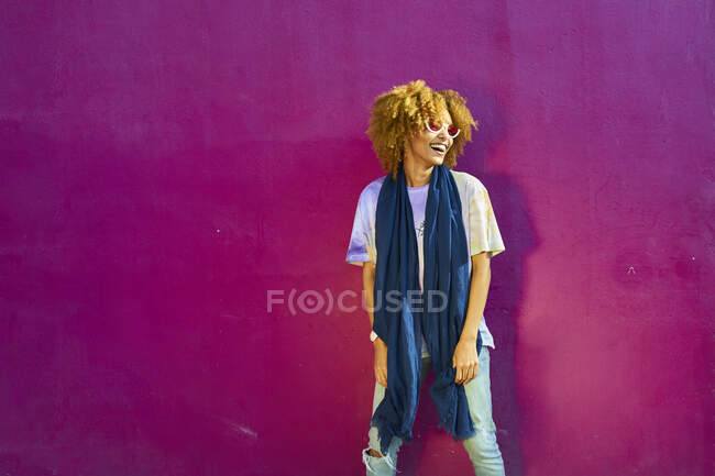 Happy woman standing before a pink wall — Stock Photo