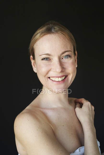 Портрет улыбающейся женщины, без бретелек, черный фон — стоковое фото