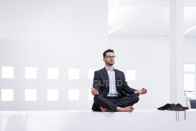 Бизнесмен, занимающийся йогой в офисе — стоковое фото