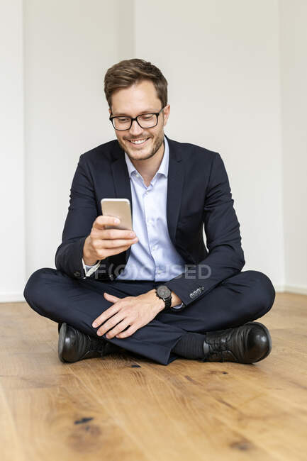 Smiling businessman sitting on the floor using cell phone — Stock Photo