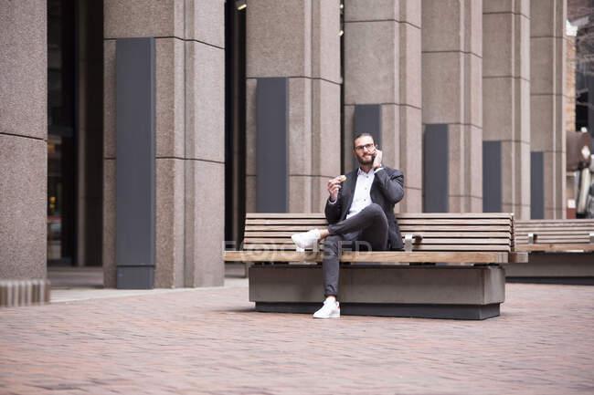 Empresário ao telefone sentado no banco comendo donut, Nova York, EUA — Fotografia de Stock