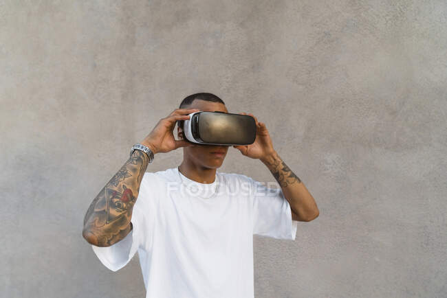 Tattooed young man using Virtual Reality Glasses looking up — Stock Photo