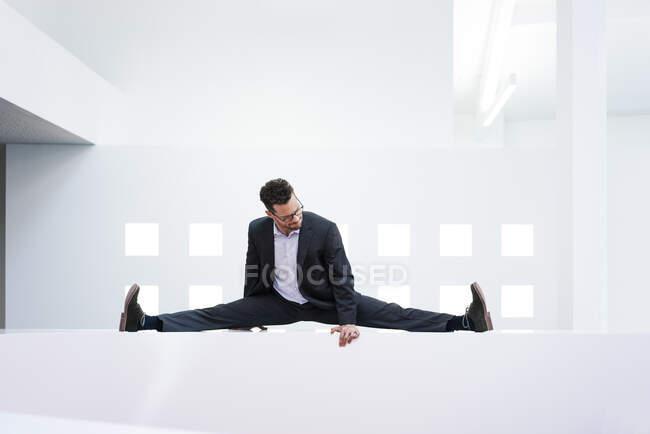 Homme d'affaires appuyé sur la réception dans le bureau — Photo de stock