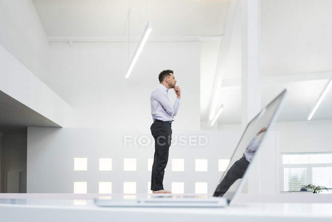 Thoughtful businessman at laptop in office — Stock Photo