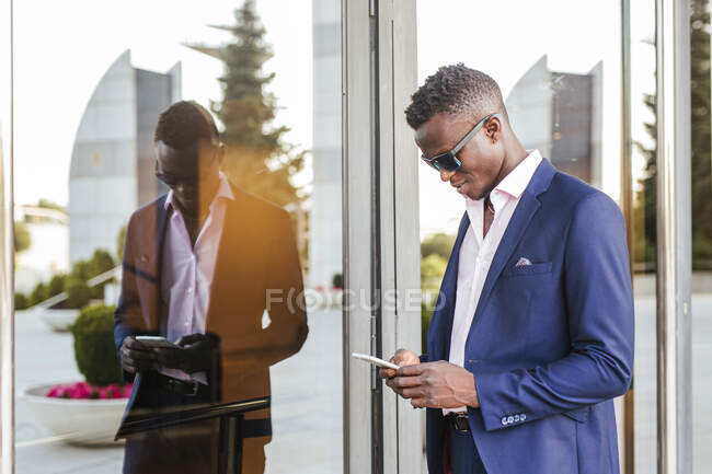 Молодий бізнесмен користується своїм смартфоном на вулиці. — стокове фото