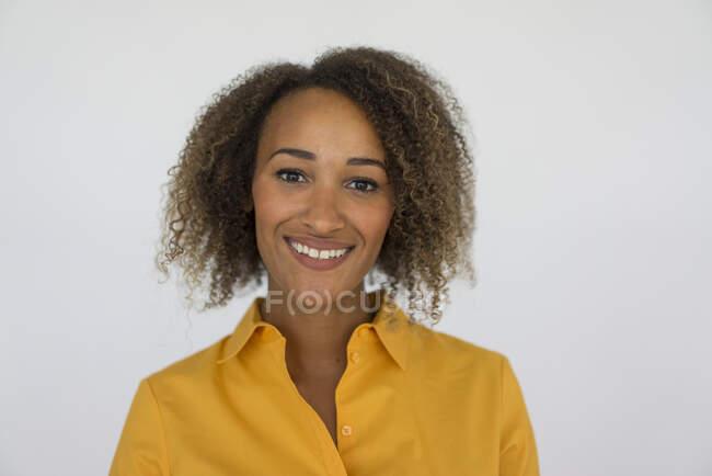 Портрет усмішки молодої жінки в жовтій сорочці. — стокове фото