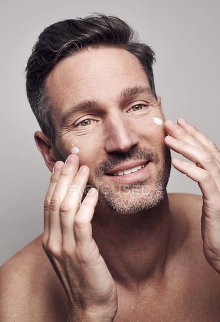 Man creaming his face — Stock Photo