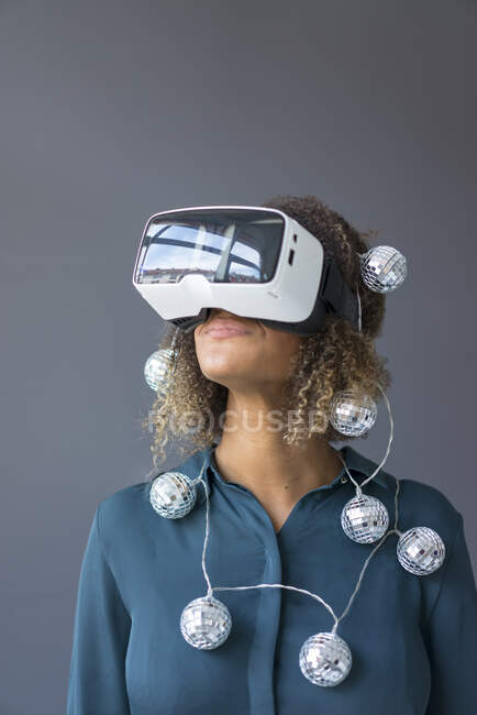 Smiling young woman with chain of lights using Virtual Reality Glasses — Stock Photo